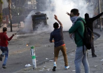Egyptian protesters gestures towards a police armored vehicle during clashes near Tahrir Square in Cairo on March 9, 2013. A court verdict over deadly football violence sparked fresh unrest in Egypt with two people killed and buildings torched in Cairo, as Islamist President Mohamed Morsi faces growing civil unrest. AFP PHOTO / MAHMOUD KHALED        (Photo credit should read MAHMOUD kHALED/AFP via Getty Images)