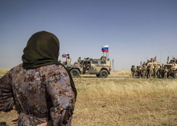 TOPSHOT - A Syrian woman looks at US and Russian soldiers in the northeastern Syrian town of al-Malikiyah (Derik) at the border with Turkey, on June 3, 2020. (Photo by DELIL SOULEIMAN / AFP) (Photo by DELIL SOULEIMAN/AFP via Getty Images)