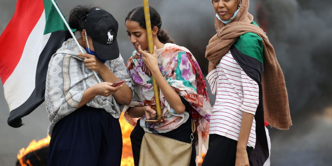 Sudanese women lift national flags by burning tyres as they take part in a demonstration on Sixty Street in the capital Khartoum, on May 23, 2020, to commemorate the first anniversary of a deadly crackdown carried out by security forces on Sudanese protesters during a sit-in outside army headquarters in the capital,  with a death toll of over a 100. (Photo by Ashraf SHAZLY / AFP) (Photo by ASHRAF SHAZLY/AFP via Getty Images)