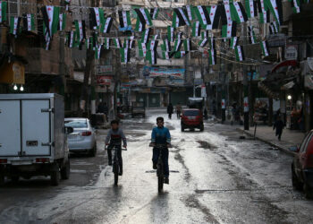 Syrian boys ride their bikes under pre-Baath Syrian flags, that was adopted by the Syrian revolution during the uprising, in the northern Syrian city of Aleppo on March 15, 2015, to mark the fourth anniversary of Syria's conflict, which began with anti-regime protests in mid-March 2011 and spiralled into a bloody war after a harsh government crackdown on demonstrators. AFP PHOTO / AMC / ZEIN AL-RIFAI        (Photo credit should read ZEIN AL-RIFAI/AFP via Getty Images)