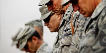 BAGHDAD, IRAQ - DECEMBER 15: U.S. military personnel bow their heads in prayer during a casing ceremony where the United States Forces- Iraq flag was retired signifying the departure of United States troops from Iraq at the former Sather Air Base on December 15, 2011 in Baghdad, Iraq. United States forces are scheduled to entirely depart Iraq by December 31, there are currently around 4,000 troops remaining in Iraq. (Photo by Mario Tama/Getty Images)