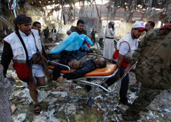 "EDITORS NOTE: Graphic content / Yemeni Red Crescent workers carry a victim on a stretcher amid the rubble of a destroyed funeral hall building following reported airstrikes by Saudi-led coalition air-planes on the capital Sanaa on October 8, 2016. Rebels in control of Yemen's capital accused the Saudi-led coalition fighting them of killing or wounding dozens of people in air strikes on Sanaa. The insurgent-controlled news site sabanews.net said that coalition planes hit a building in the capital where people had gathered to mourn the death of an official, resulting in ""dozens of dead or wounded"". / AFP / MOHAMMED HUWAIS        (Photo credit should read MOHAMMED HUWAIS/AFP via Getty Images)"