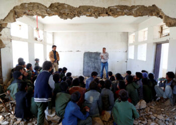 IBB, YEMEN - DECEMBER 16: Yemeni students are seen listening to their teacher inside a wreckage of their school, at Ar Radmah district of Ibb, Yemen on December 16, 2019. Yemeni children, living in the district of the Ibb province in the south of capital Sanaa are trying to continue their education in the shadow of the war at the classrooms without heating stoves and benches. Due to the ongoing civil war and conflicts for almost 5 years, lots of schools in the city have been damaged or ruined.   (Photo by Mohammed Hamoud/Anadolu Agency via Getty Images)