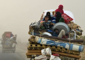 TOPSHOT - Displaced Syrians from Deir Ezzor head to refugee camps on the outskirts of Raqa on September 24, 2017 as Syrian fighters backed by US special forces are battling to clear the last remaining Islamic State group jihadists holed up in their crumbling stronghold. / AFP PHOTO / BULENT KILIC        (Photo credit should read BULENT KILIC/AFP via Getty Images)