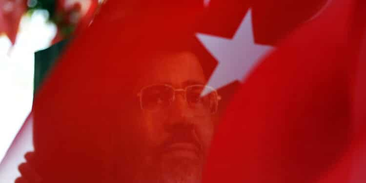 "A portait of ousted Egyptian president Mohamed Morsi is seen through a Turkish flag during a rally on August 25, 2013 in Istanbul to support ousted Egyptian president Morsi and protest against killings in Syria and Egypt. The ""Rabia sign"" has become a symbol to remember the massacre in Egypt at the Rabaa al-Adawiya Square where the anti-coup protests took place.          AFP PHOTO / BULENT KILIC        (Photo credit should read BULENT KILIC/AFP via Getty Images)"