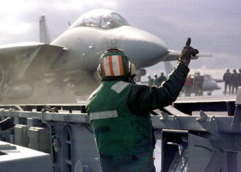 """A F-14B """"Tomcat"""" stands ready to launch from the aircraft carrier USS Enterprise November 7, 1998 which is headed to the Persian Gulf. The United States has beefed up its military strength in the Gulf and is threatening airstrikes in an attempt to force Iraq to allow inspections by UNSCOM, which is responsible for eliminating Iraq's weapons of mass destruction. (photo by US Navy)"""