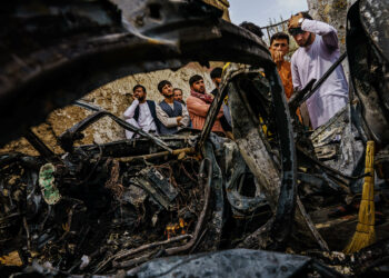KABUL, AFGHANISTAN -- AUGUST 30, 2021: Relatives and neighbors of the Ahmadi family gathered around the incinerated husk of a vehicle targeted and hit earlier Sunday afternoon by an American drone strike, which killed 10 people including children, in Kabul, Afghanistan, Monday, Aug. 30, 2021. (MARCUS YAM / LOS ANGELES TIMES)