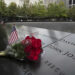 NEW YORK, NY - SEPTEMBER 08: A U.S. flag and a flower are placed near a victim's name at the September 11 Memorial at Ground Zero on September 8, 2021 in New York, United States. (Photo by Liao Pan/China News Service via Getty Images)